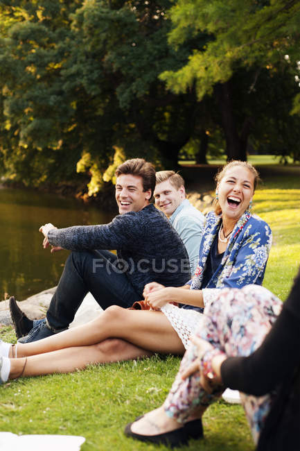Happy friends enjoying at riverbank — Stock Photo