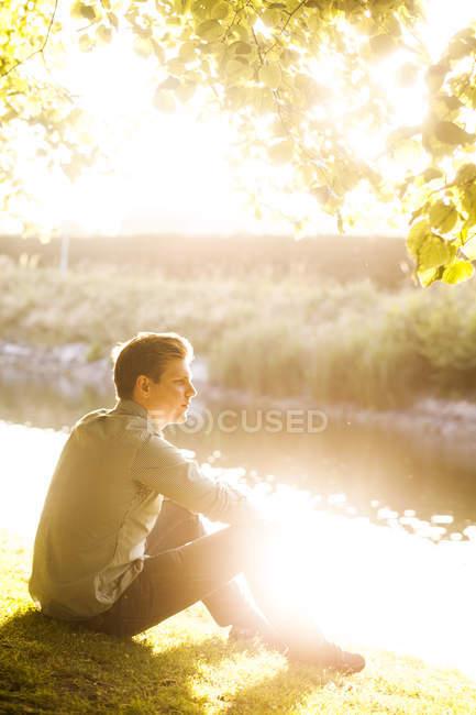 Uomo seduto alla riva del fiume — Foto stock