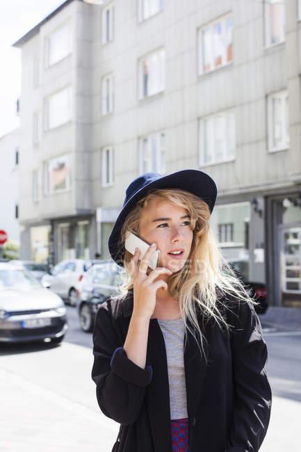 Donna che utilizza il telefono cellulare in città — Foto stock