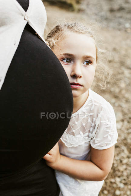 Thoughtful girl leaning on pregnant belly — Stock Photo