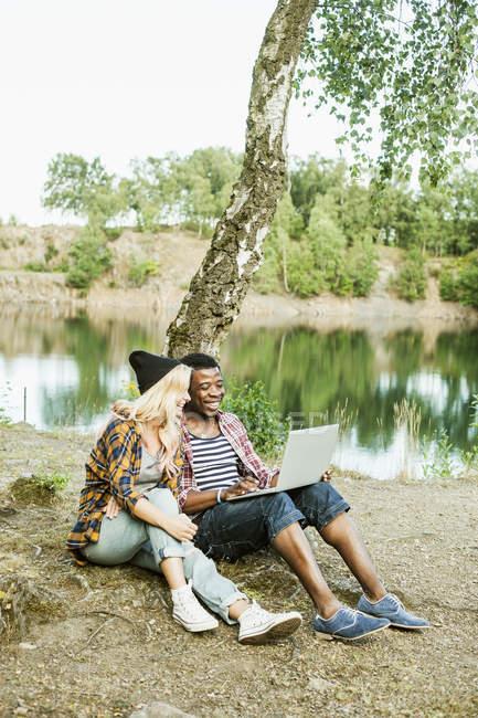 Paar mit Laptop am Seeufer — Stockfoto