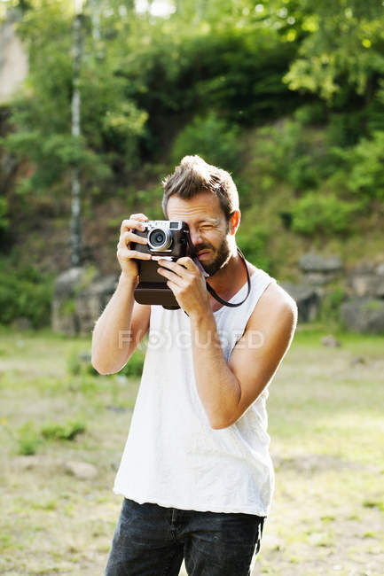 Man photographing through old-fashioned camera — Stock Photo