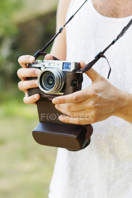 Man holding vintage camera in forest — Stock Photo