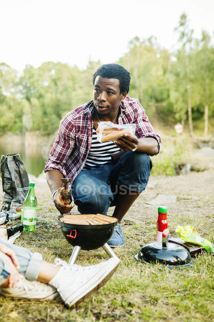 Man holding sausages while barbecuing — Stock Photo