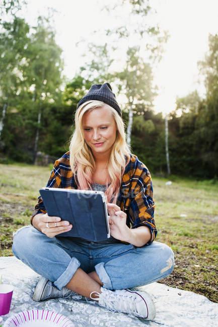 Женщина с помощью планшета на одеяло для пикника — стоковое фото