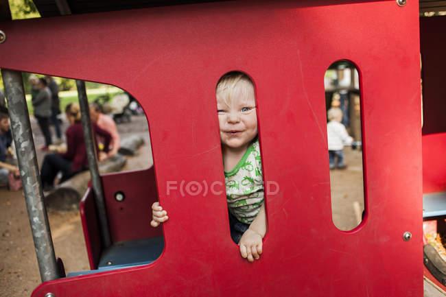 Garçon regardant à travers le train miniature — Photo de stock