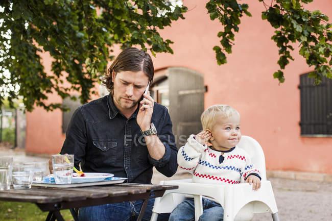 Homem alimentando bebê menina e falando no smartphone — Fotografia de Stock