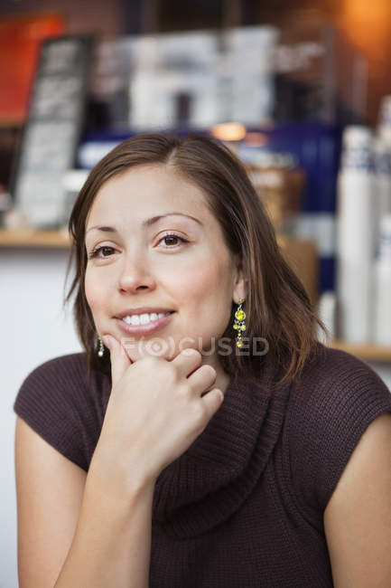 Woman with hand on chin in cafe — Stock Photo