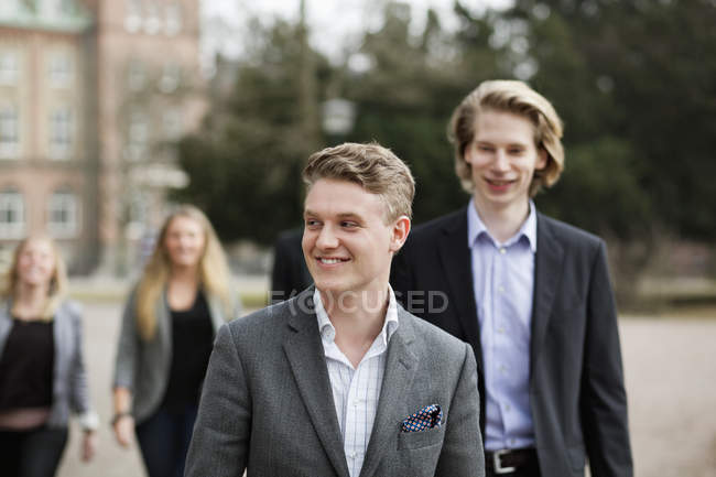 Happy businessmen walking outdoors — Stock Photo