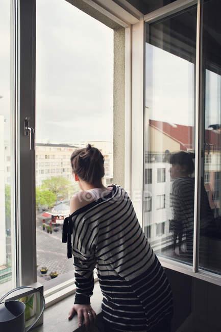 Frau schaut durch Fenster — Stockfoto