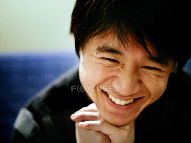 Портрет улыбающегося азиата с руками на подбородке и закрытыми глазами — стоковое фото