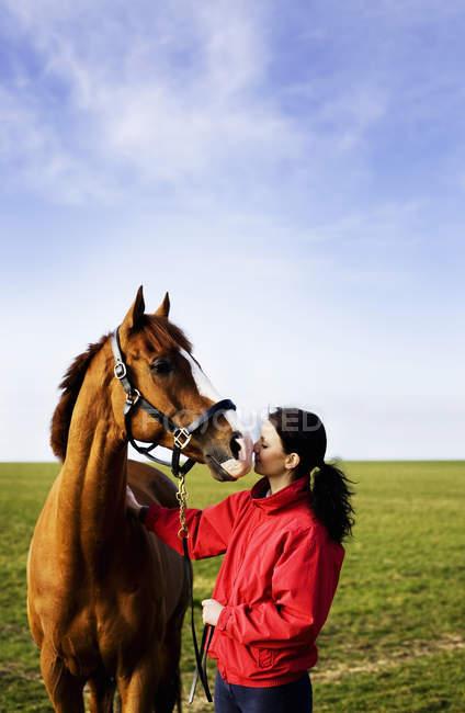Вид збоку жінки цілуватися коні в поле під чисте небо — стокове фото