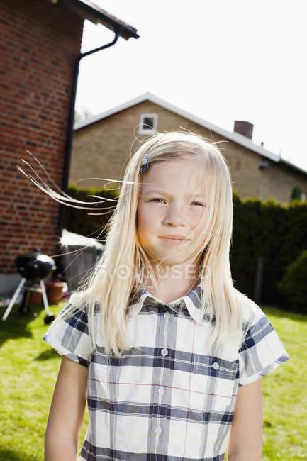 Блондинка стоит на заднем дворе в солнечный день — стоковое фото