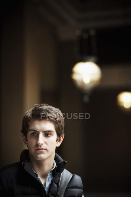 Young man standing indoors — Stock Photo