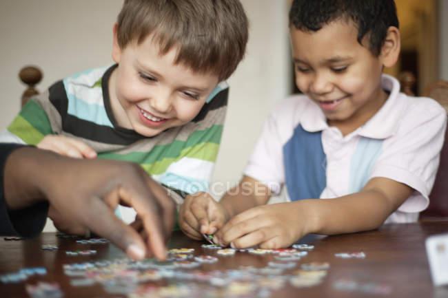 Счастливые мальчики играют в пазл — стоковое фото