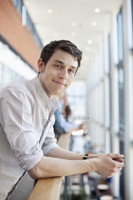 man leaning on railing at shopping mall stock photo 151420260