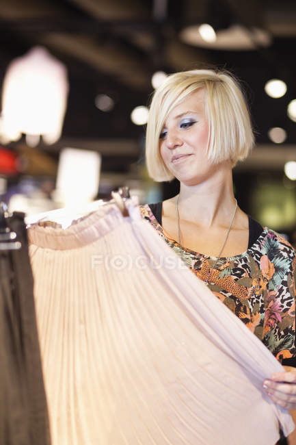Woman looking at skirt in shopping mall — Stock Photo
