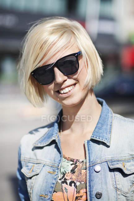 Mujer que lleva gafas de sol en la ciudad de - foto de stock