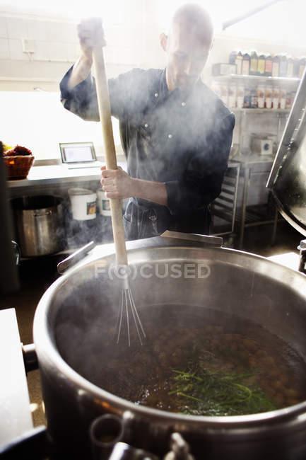 Male chef stirring food — Stock Photo