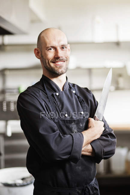 Confident male chef holding knife — Stock Photo