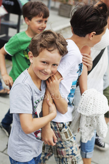 Boy with brothers and mother on street — Stock Photo