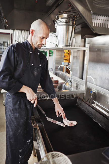 Chef cooking meat in restaurant kitchen — Stock Photo