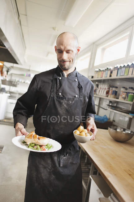 Chef serving food in restaurant kitchen — Stock Photo