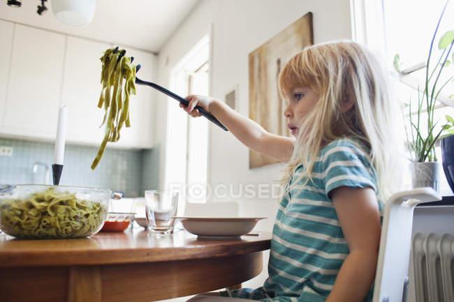 Girl holding tagliatelle pasta — Stock Photo