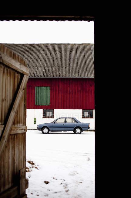 Auto e casa visto attraverso porta — Foto stock