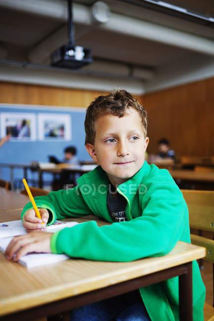 Garçon assis au bureau — Photo de stock