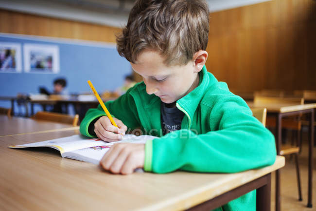 Boy writing in book — Stock Photo