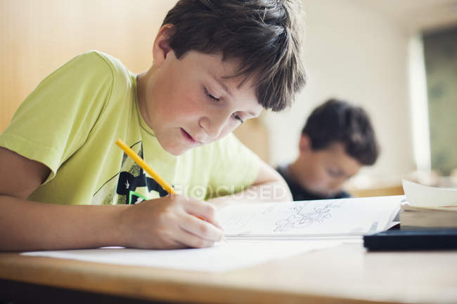 Хлопчик, написання книги — стокове фото