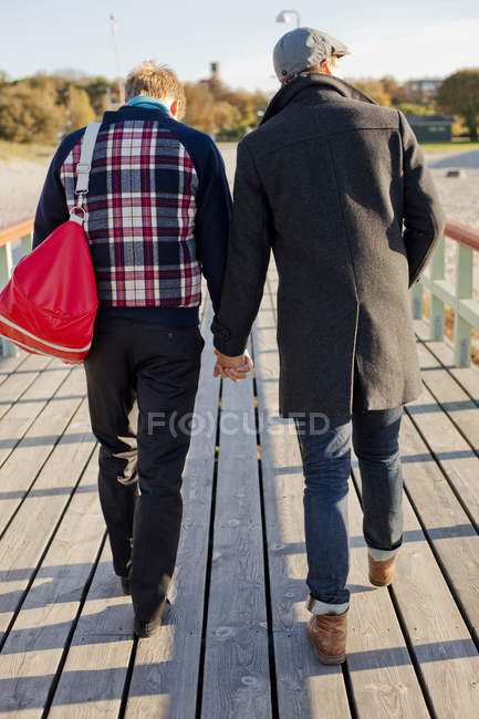 Gay couple walking on boardwalk — Stock Photo