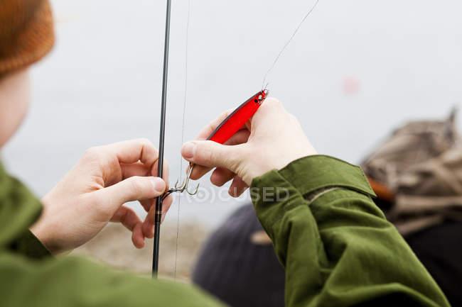 Подросток, применяя крюк на удочку — стоковое фото