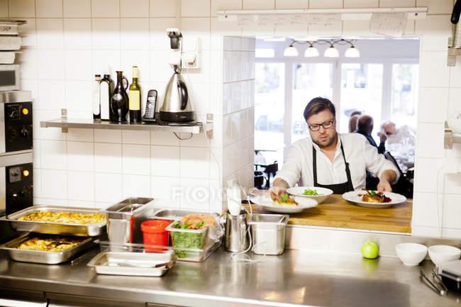 Chef que sirve platos - foto de stock