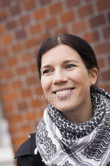 Woman looking away against brick wall — Stock Photo