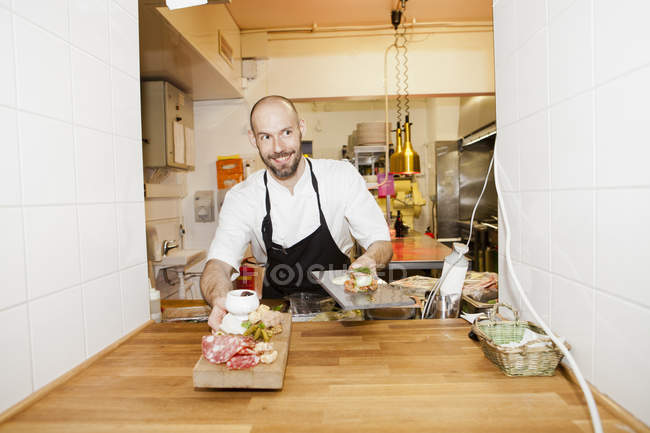 Chef serving dishes at commercial kitchen — Stock Photo
