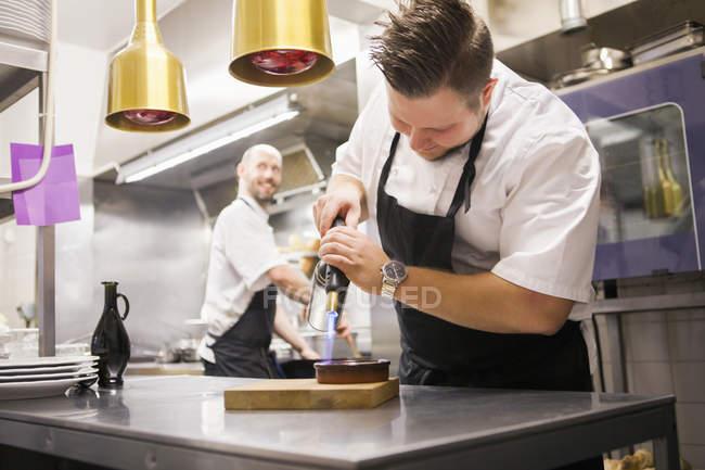 Chef caramelizing creme brulee — Stock Photo