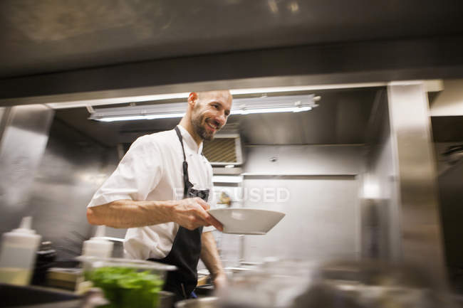 Chef holding dish while walking at kitchen — Stock Photo