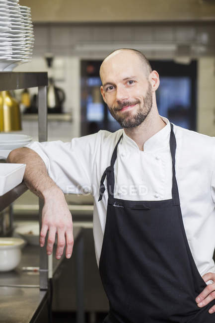 Chef leaning on shelf at commercial kitchen — Stock Photo