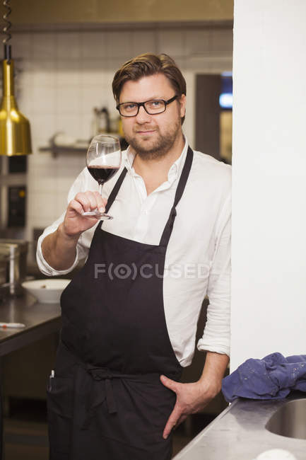 Confident chef holding red wineglass — Stock Photo