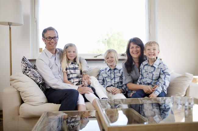 Family With Three Children Sitting On Sofa In Home Interior U2014 Stock Photo