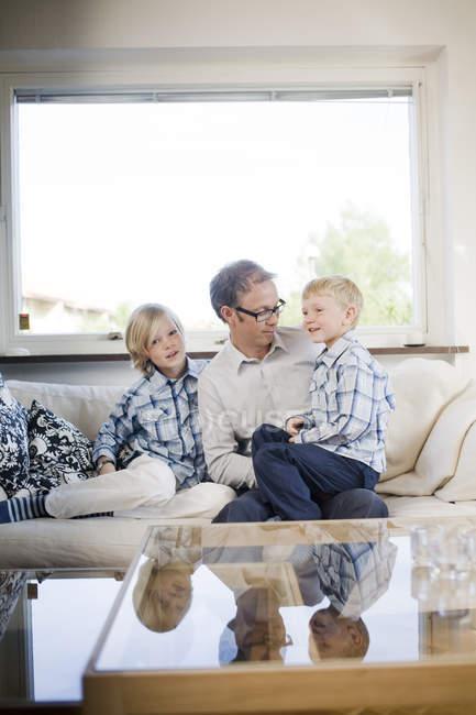 Padre Con Due Figli Seduti Sul Divano Davanti Alla Finestra A Casa