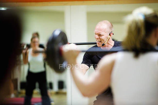 Cheerful instructor lifting barbell — Stock Photo