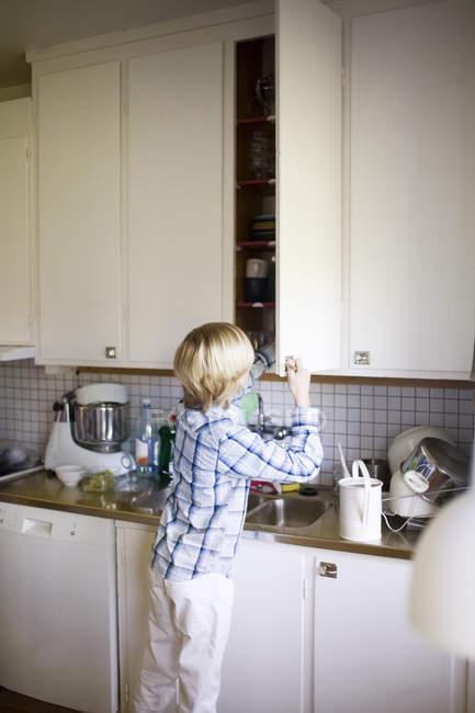 Задній вид хлопчик відкриття дверей шафи кухні на дому — стокове фото