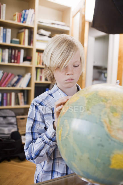 Serious boy looking at globe in living room interior — Stock Photo