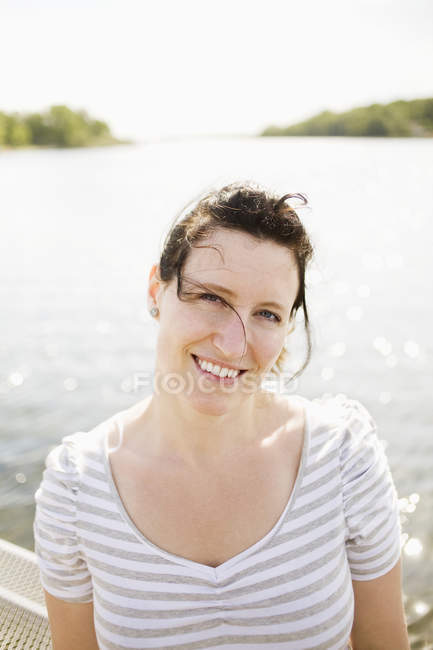 Woman against river on sunny day — Stock Photo