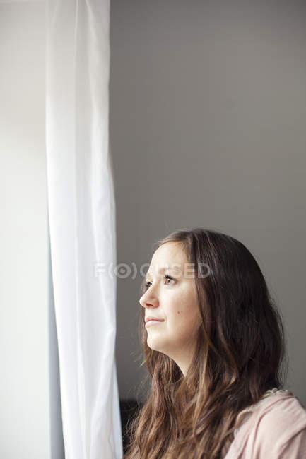 Donna in piedi vicino alla tenda a casa — Foto stock