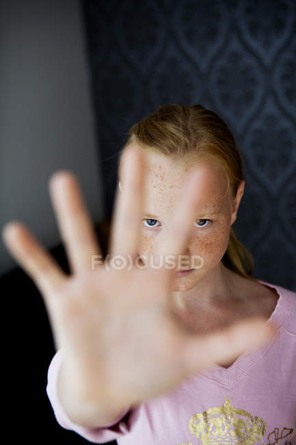 Portrait of girl gesturing stop sign at home — Stock Photo