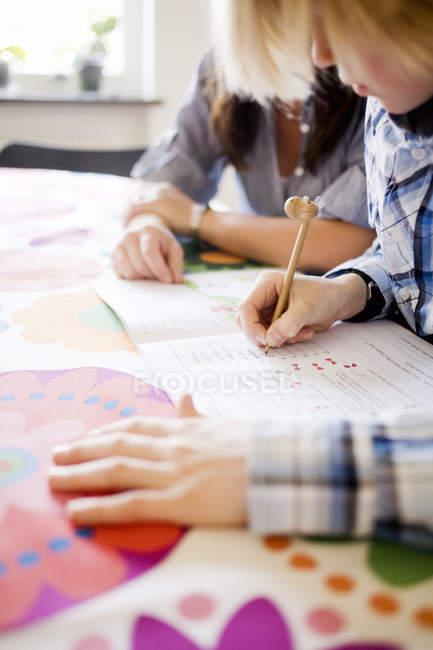 Зменшеному вигляді хлопчик писати в ноутбуці при матері дивляться — стокове фото